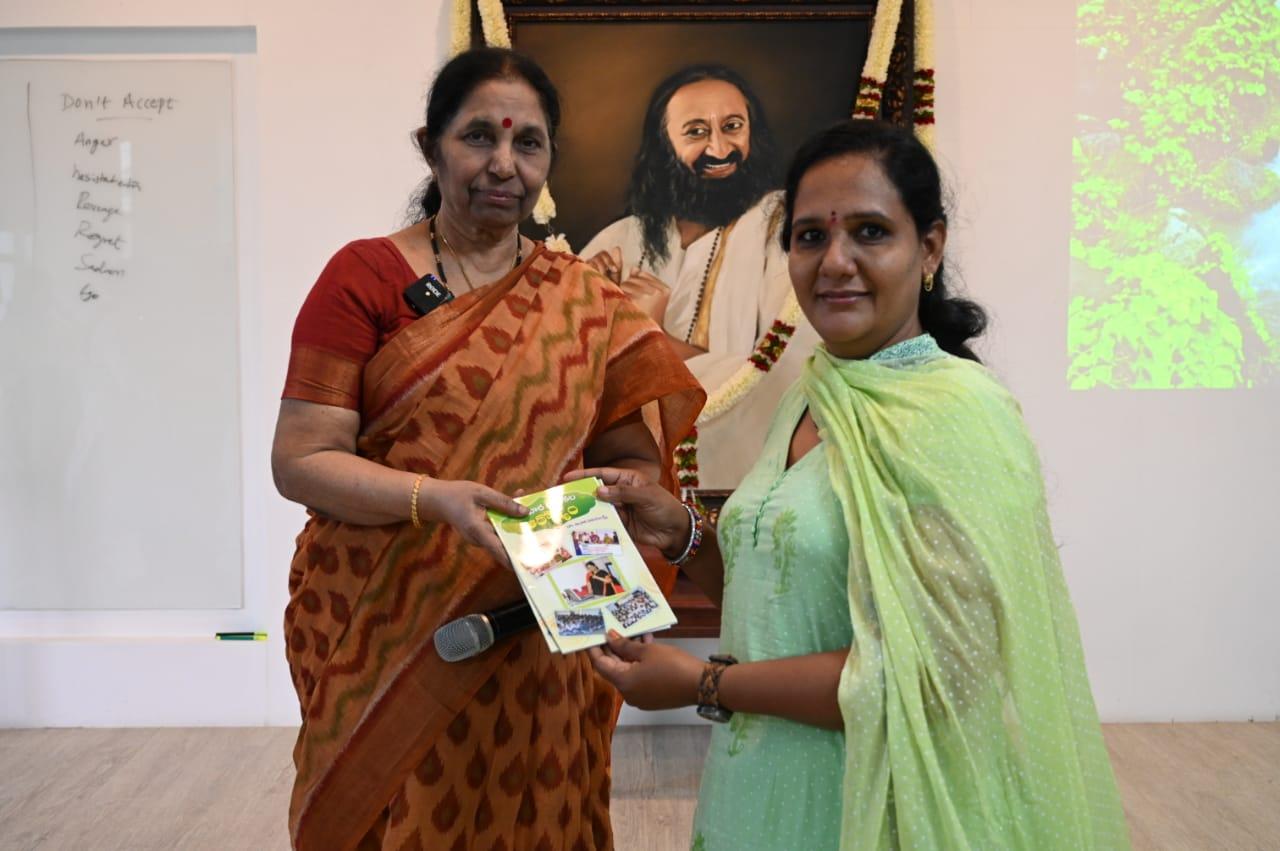 Dr.AluriVijayalakshmi gifting a book